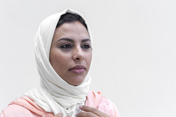 Close up of woman in hijab standing against white background