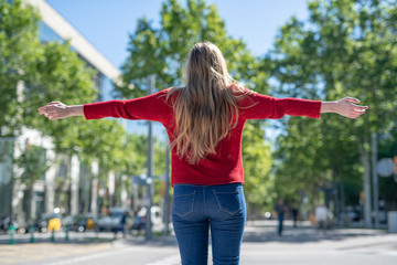 Back view of blonde girl with open arms symbolically embracing the city