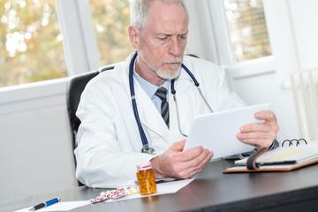 Senior doctor using tablet