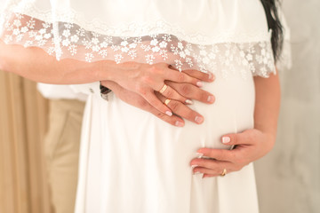Pregnant couple. Husband touching his wife belly. Woman is pregnant. Concept happy family. Close up
