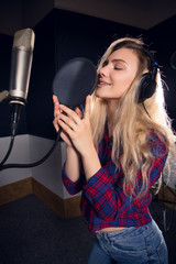 Express yourself in music! Smiling attractive trendy female singer with microphone recording her new album in the studio.