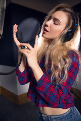 Successful recording! Close up portrait of the beautiful young blonde girl recording her new song in the electronic studio.