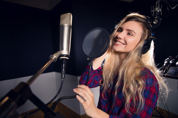 Music is all around! Young cheerful pretty smiling blonde woman recording a song in a professional studio in headphones.