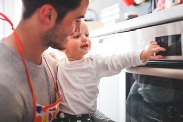 Young father cooking and takes care of little child in the kitchen at home
