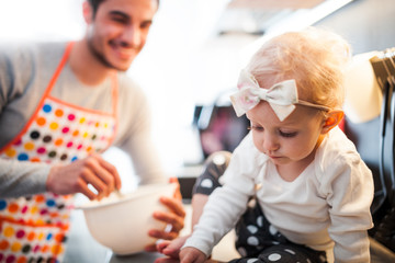 Smiling dad preparing food in the kitchen and takes care of his little daughter, family lifestyle