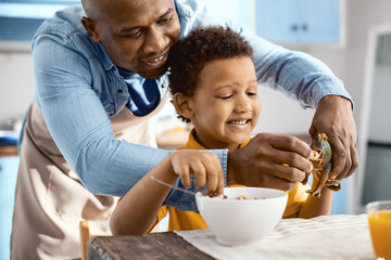 Best pastime. Happy young father feeding cereals to the toy dinosaur of his son and smiling happily while the boy having breakfast