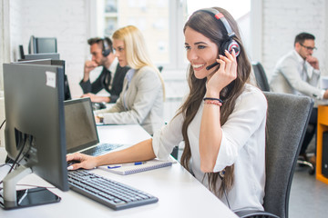 Friendly smiling woman call center operator with headset using computer at office Fototapete