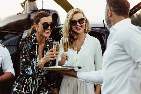 Man greets female friends with wine
