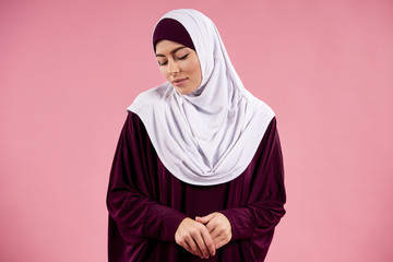 Arabian young woman in hijab is looking down.