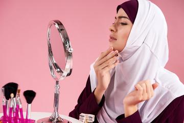 Attractive Arabian woman in hijab looks on face