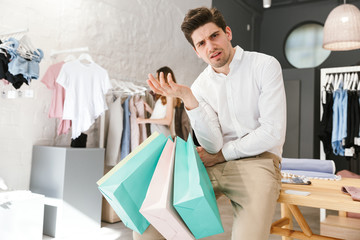 Confused man sitting and holding shopping bags