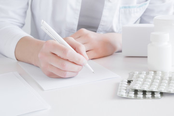 Doctor writing prescription for treatment of patient. Visit to physician at office. Medical and pharmacy concept. Different medicines on the table.