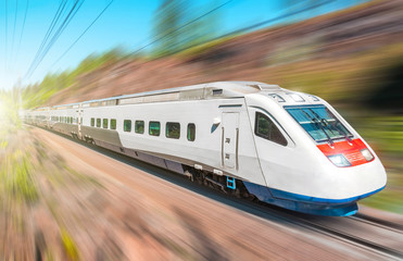High-speed electric train with motion blur. The railway passes in a rocky canyon in the forest