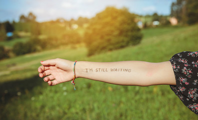 Closeup of female arm with the text -I'm still waiting- written in the skin over a nature background
