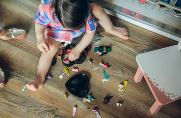 Top view of cute baby girl playing with hair clips collection sitting in a wooden floor at home