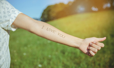 Closeup of male arm with the text -I love you- written in the skin over a sunny nature background