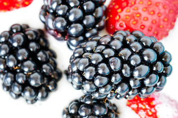 Close up picture of blackberries and strawberries in yogurt, shallow depth of field.