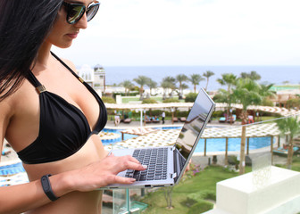 I work even on vacation. Attractive young woman in black bikini and wearing glasses with laptop on the background of the resort. Search for a holiday. Work on the Internet.