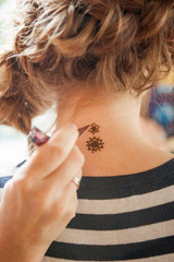 Drawing mehndi on the girl's neck