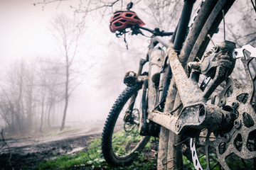 Mountain bike and helmet in autumn woods, dirty bicycle