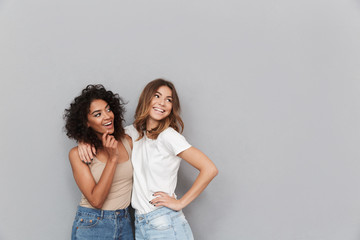 Portrait of two happy young women standing Wall mural