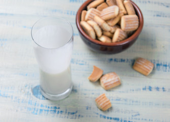Kefir (sour milk product) in a glass and cookies on a wooden background. Snack during the day.