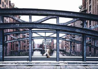 back view of woman wearing long coat standing on windy bridge in old warehouse district Speicherstadt in Hamburg, Germany