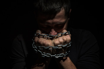 Hands bound in metal chains on a black background