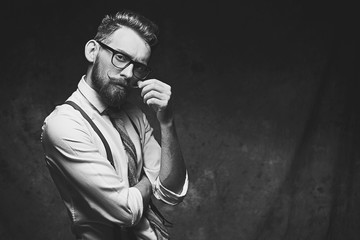 Young stylish hipster with cool hairstyle and beard dressed in white shirt and suspenders is thinking of a new creative idea looking at viewer Wall mural