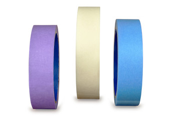 Three multi-colored roll of paint tape on an whitebackground.