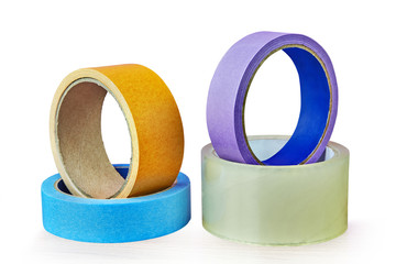 Four rolls of adhesive tape lying on table,  white background.