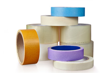 Coils of plastic and paper adhesive tape, on  white.
