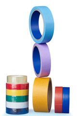 Multi-colored rollers of adhesive tape on  white background.
