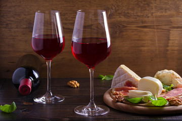 Glasses and bottle of wine with cheese, bread, nuts and jamon or prosciutto on dark wooden background. Wine and food concept