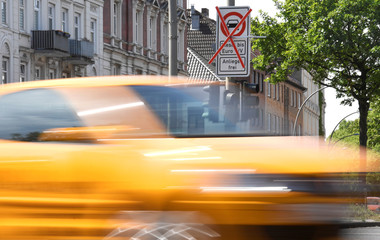 A car passes a traffic sign showing a ban on diesel cars at the Max-Brauer Allee in downtown Hamburg
