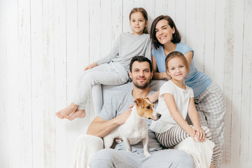 Family portrait. Happy parents with their two daughters and dog pose together against white background, spend free time at home, being in good mood. Mother, father and small sisters pose indoor