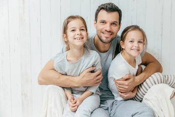 Portrait of happy young father embraces his two daughters, loves them very much, pose together at home. Single dad with beautiful femle children have cheerful expressions. Fatherhood concept