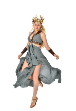 full length portrait of pretty blonde lady wearing fantasy toga gown,  and holding a bow and arrow. standing pose on white background.