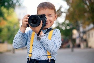 Boy makes pictures on film retro style digital camera