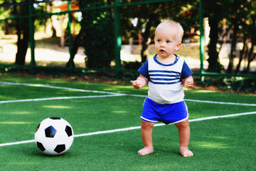 Little boy in blue shorts playing with soccer ball at sports ground. Blonde child in sports uniform standing at football field with a ball. Summer kids activity concept