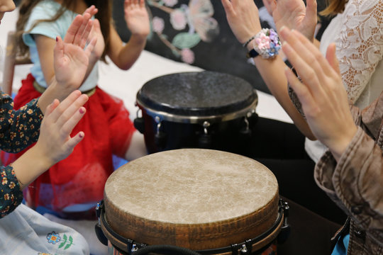 Kids play jembe drum in a montessori music therapy classroom with parents, hands close up