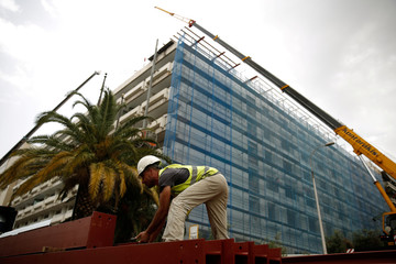A construction worker stands on a crane during renovation works at a building expected to open as a Grand Hyatt Hotel in Athens