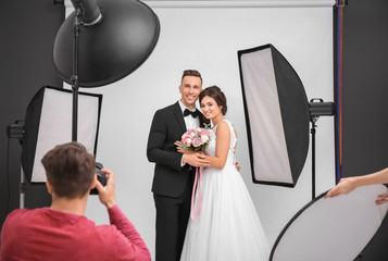 Professional photographer taking photo of wedding couple in studio