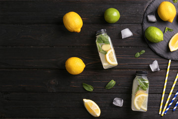 Flat lay composition with detox lemonade and ingredients on wooden background