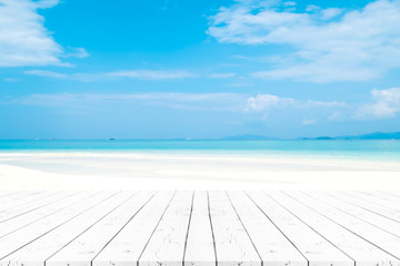 Perspective white pearl wooden table on top over blur sea in sunny day background. Beautiful sea and clouds in Thailand on summer, can be used mock up for montage products display or design layout.