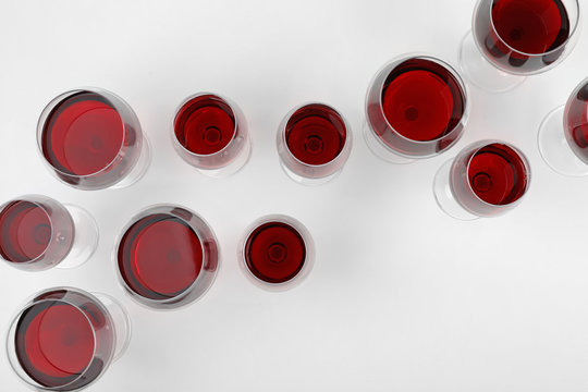Glass of expensive red wine on light background, top view