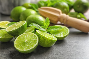 Ripe limes and mint on grey background. Refreshing beverage recipe