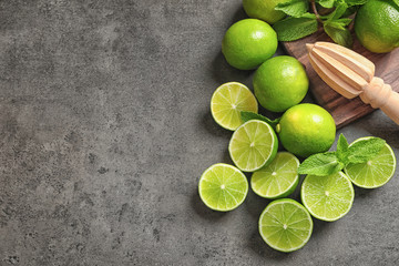 Flat lay composition with ripe limes, mint and juicer on grey background. Refreshing beverage recipe