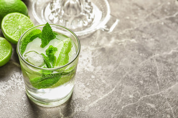Refreshing beverage with mint and lime in glass on table