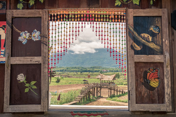 landscape of mountains through traditional wooden window in thailand